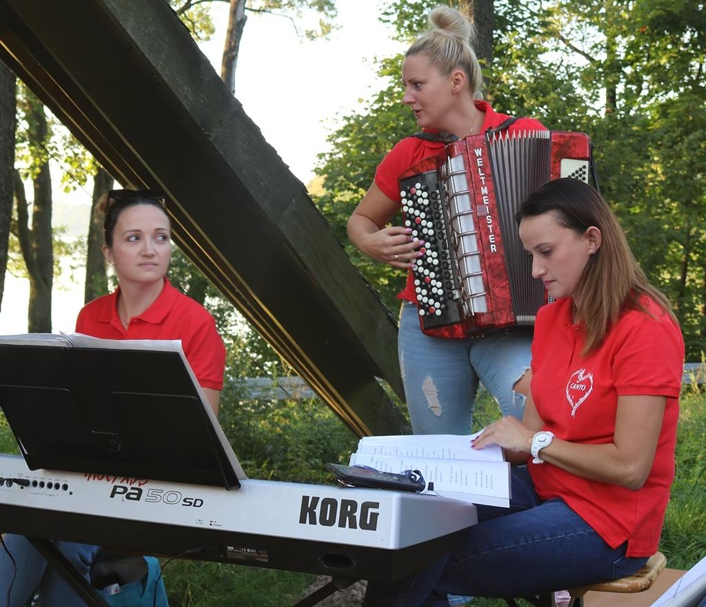 Wokalistki zespołu wokalnego CANTO. W środku stoi prowadząca grupę trzymająca w dłoniach akordeon. Przed nią stoi pianino elektryczne, przy którym siedzą dwie inne członkinie zespołu.
