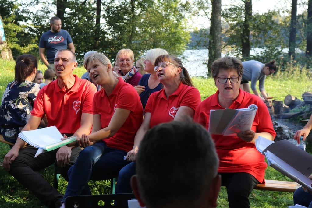 Zdjęcie przedstawia członków Zespołu Wokalnego CANTO śpiewających piosenki ogniskowe. Za nimi widoczni są słuchacze,tj. uczestnicy wydarzenia