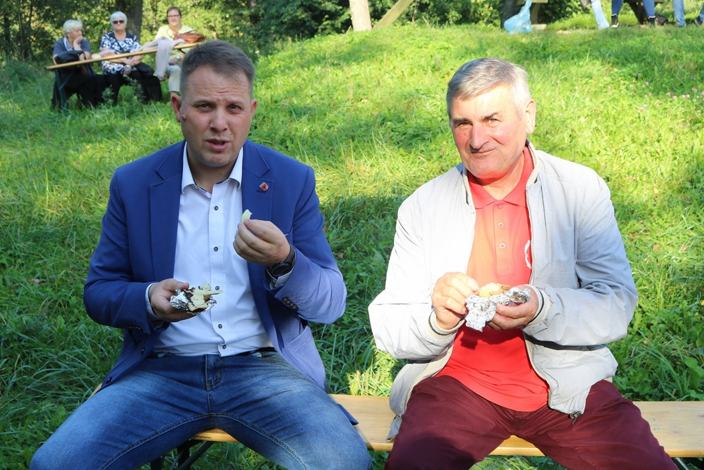 Zdjęcie przedstawia siedzących na ławce - Wójta Gminy Filipów oraz członka zzespołu wokalnego CANTO jedzących upieczone w ognisku ziemniaki