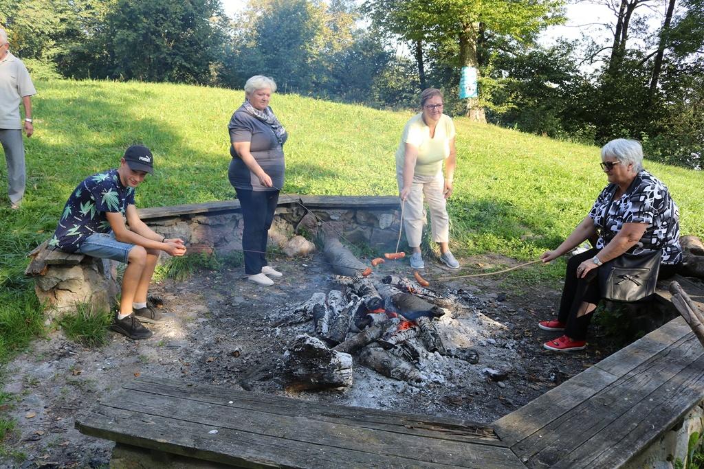 Zdjęcie przedstawia cztery osoby zgromadzone wkoło ogniska. Trzy dorosłe kobiety oraz nastolatek trzymają nad ogniskiem kije, na które nabite są kiełbaski.